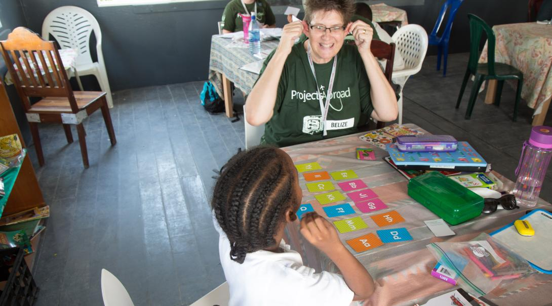 A teaching volunteer taking a career break, works with a student in Belize to improve her literacy